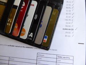 carteira com cartões de crédito em cima de planilha representando cartão Caixa para negativado