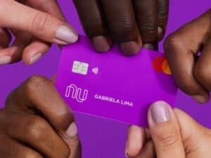 Imagem de várias mãos segurando um cartão de cor roxa, simbolizando o cartão Nubank Black