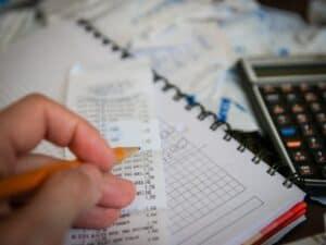 mão de um homem segura um lápis sobre uma nota com vários valores. Embaixo da nota há um caderno e, ao lado, uma calculadora. organização é essencial na hora de enviar documentos para o IRPF 2021