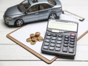 uma prancheta com papéis tem em cima uma calculadora, umas moedas e um carro de brinquedo