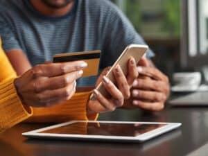Imagem de um homem e uma mulher segurando um cartão em uma mão e um celular em outra para simbolizar nosso conteúdo que ensina como fazer cartão de crédito pela internet