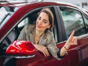 mulher de terno sentada no banco de motorista de um carro vermelho sorri e faz sinal de positivo