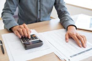 homem sentado a uma mesa faz cálculos em uma calculadora e confere os números em vários papéis que estão à sua frente