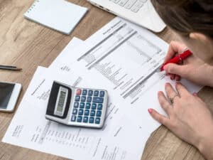em uma mesa, a mão de uma mulher assinando papéis com uma calculadora do lado