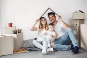 mãe, pai e filho sentados no chão de uma casa. Os pais seguram uma madeira que simula uma casa para sinalizar a compra recente. Ao lado deles, várias caixas de mudança