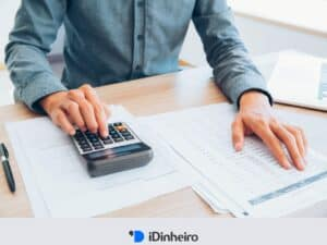 pessoa usando uma calculadora representando como declarar fundos de investimento no imposto de renda