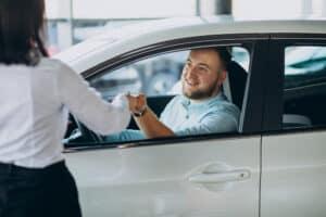 homem está no banco do motorista de um carro branco e recebe algo, que parece uma chave, de uma mulher que está fora do veículo
