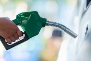 mão segurando bomba de gasolina, representando reajuste no preço da gasolina