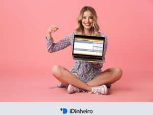 mulher apontando para laptop que mostra home broker na tela
