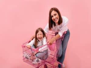 Mulher empurra carrinho com criança dentro para usarem listas de compras de supermercado