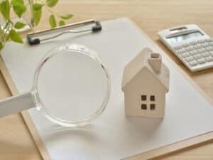 Em uma mesa, uma prancheta com uma pequena maquete de casa e uma lupa. Ao lado, uma calculadora.