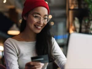 Imagem de uma mulher usando um computador e seu cartão de crédito enquanto provavelmente faz uma pesquisa, usamos a foto para simbolizar o post sobre melhores cartões de crédito sem anuidade