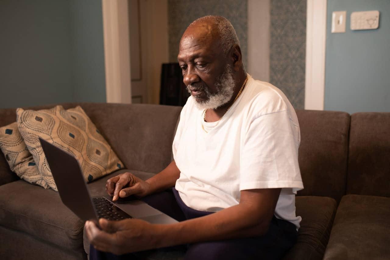Um homem idoso segurando um notebook, sentado no sofá