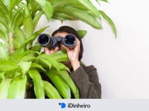 mulher com binóculos atrás de planta, representando reserva de oportunidade