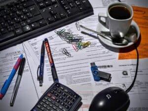 mesa com notebook, canetas, calculadora, clips e café representando seguro de vida no imposto de renda