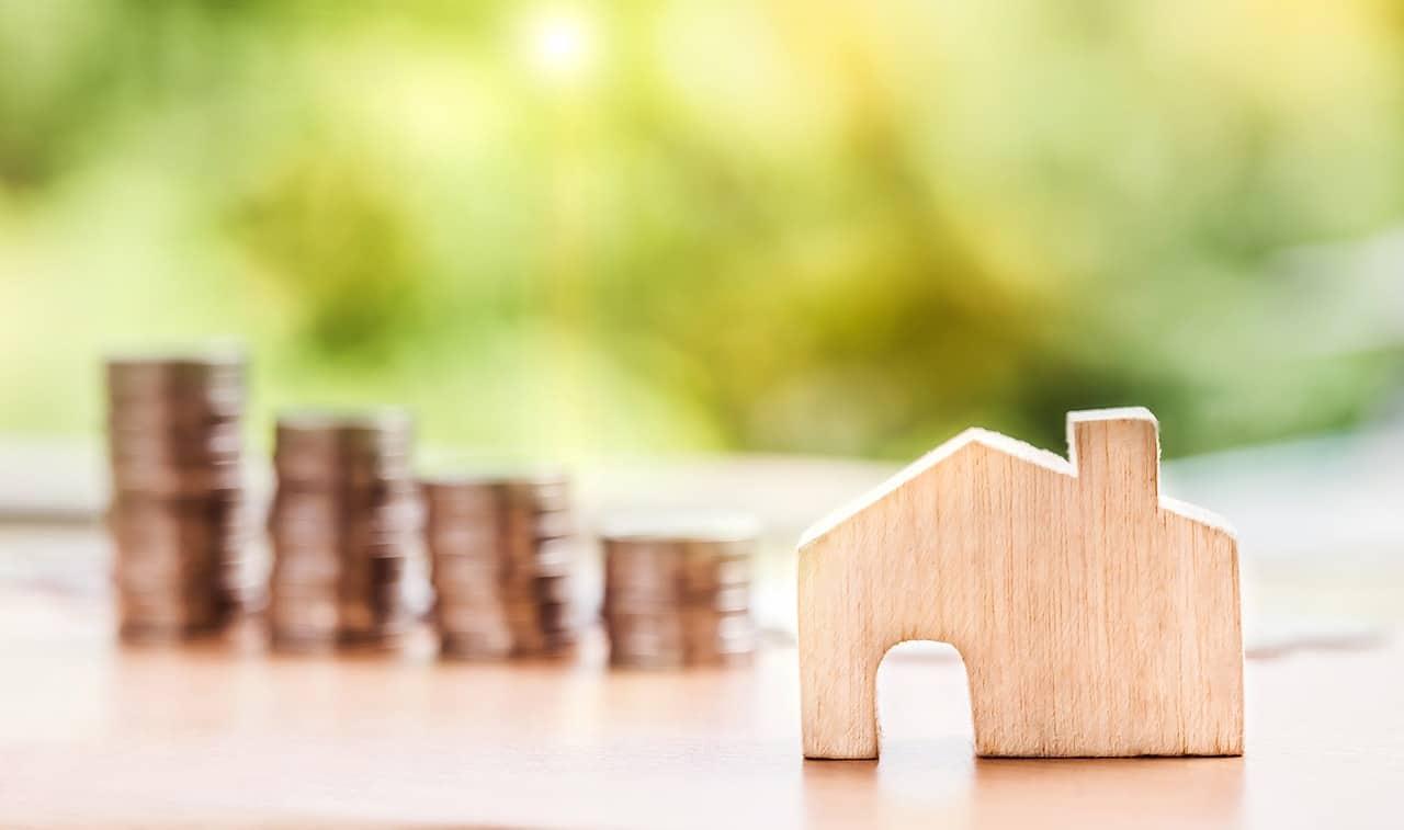 Uma miniatura de madeira no formato de fachada de casa com pilhas de moedas ao fundo