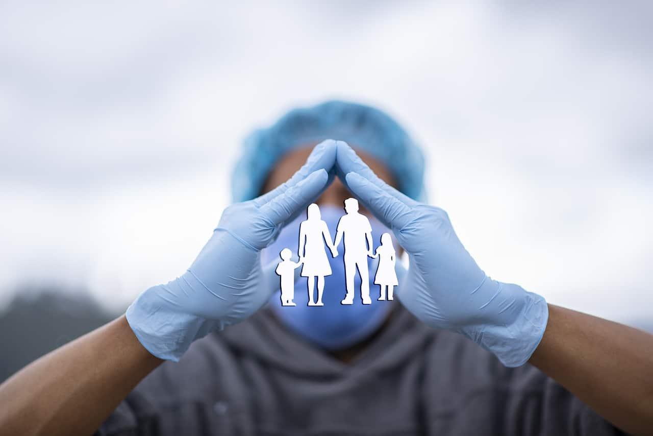 Profissional da saúde com as mãos em formato de telhado, protegendo uma família