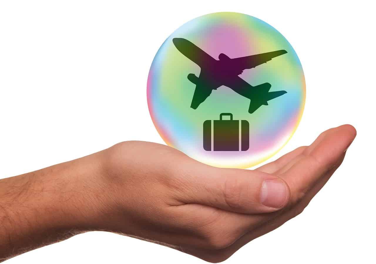 uma mala e um avião dentro de uma bolha, que é amparada por uma mão em formato de concha