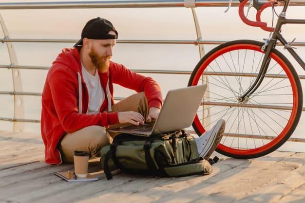 homem que optou trabalhar como freelancer usa o laptop ao lado de sua bicicleta