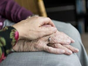 mão segurando mãos de idoso representando 13° salário para aposentados