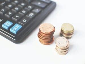 calculadora do lado de três montinhos de moedas