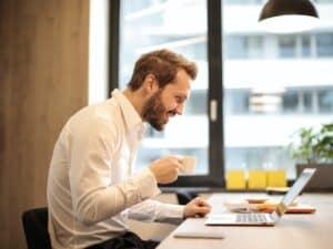 Imagem de um homem usando seu notebook e tomando um café, está lendo algo no computador. Usamos a imagem para ilustrar nosso conteúdo sobre a tabela IPA-M 2021