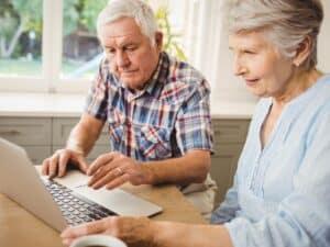 Imagem de dois idosos usando o computador para representar nosso post sobre a tabela IPCA