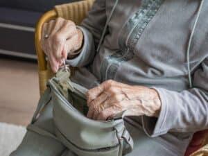 idoso colocando chaves em bolsa no colo representando antecipação de 13º salário de aposentados