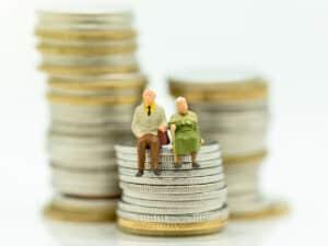 duas miniaturas de idosos estão sentados em colunas de moedas. a imagem representa como se aposentar em 2021