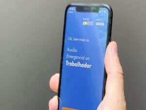 mão segurando aplicativo com tela aberta no app Caixa TEM representando erro auxílio emergencial em 2021