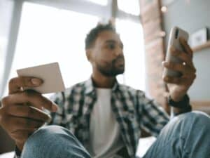 homem segurando cartão e celular, entendendo como evitar dívidas ao recorrer ao crédito