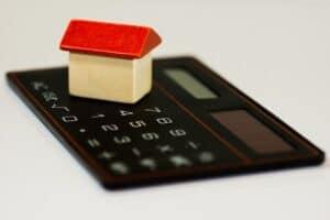uma pequena peça em formato de casa em cima de uma calculadora
