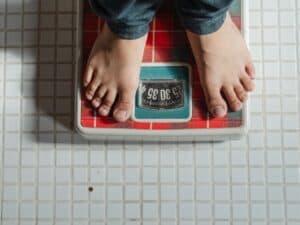 Imagem de uma pessoa em cima de uma balança, buscando calcular o peso ideal