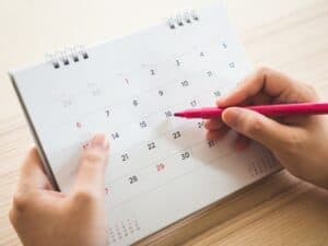 Imagem de uma pessoa usando um calendário para saber sobre o cálculo de dia da semana