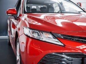 close em faróis de carro vermelho representando espera para comprar um carro