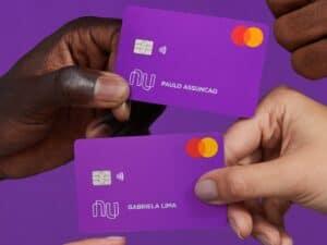 mãos segurando cartões nubank, que iniciou investimentos