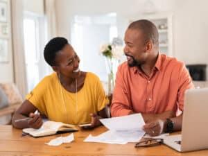 um casal sorridente com notebook e papeis na mão