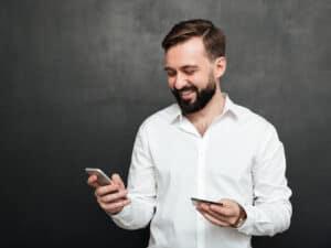 homem segurando celular, representando conta de luz com cashback
