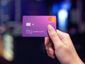 mão segurando cartão do nubank, que permitirá parcelamento de compras