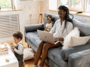 uma mulher está sentada no sofá com um computador no colo. ao seu redor, duas crianças pequenas brincam. a imagem representa os direitos dos trabalhadores durante o trabalho remoto