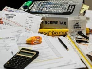livros, papéis, calculadora e caneta representando prazo para entrega da declaração do IR