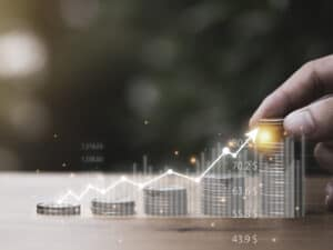 pessoa montando pilhas de moedas, representando inflação em abril