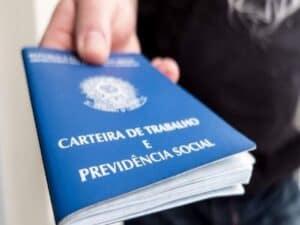 mão entregando carteira de trabalho representando programa de redução de jornada e salário