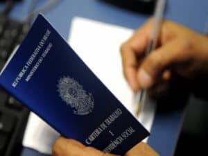 uma das mãos segurando carteira de trabalho e outra assinando documento representando seguro-desemprego em poupança social digital