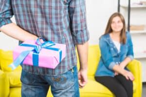 homem em pé e de costas segura um presente na parte de trás do seu corpo. Ele está de frente para uma mulher sorrindo, que está sentada em um sofá amarelo