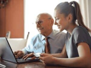 jovem e idoso em computador, representando 13º antecipado