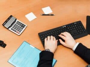 Salário CLT x PJ: imagem de duas mãos brancas de uma pessoa vestida com terno encostando em um teclado, com uma calculadora e papeis ao lado