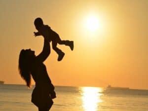 mãe levanta criança em praia durante pôr do sol representando Dia das Mães