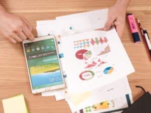 Imagem que simboliza o capital de giro com uma pessoa segurando papéis com gráficos financeiros em uma mesa