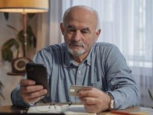 cartão corporativo: imagem de um homem sentado e olhando para um celular com um cartão na mão